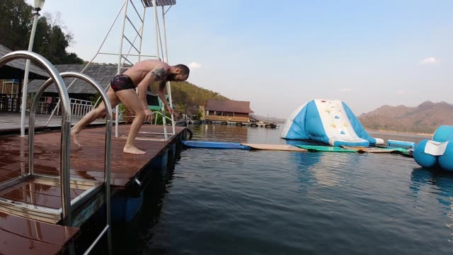 slow motion young man doing funny backflip into the lake - swimming shorts stock videos & royalty-free footage