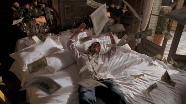 vídeos de stock e filmes b-roll de slow motion young man falling back onto bed and throwing fistfuls of money in air / bills floating down - sorte