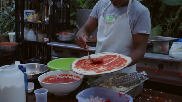 slow motion: young man putting sauce on uncooked pizza base in outdoor kitchen in el limon, dominican republic - zutaten stock-videos und b-roll-filmmaterial