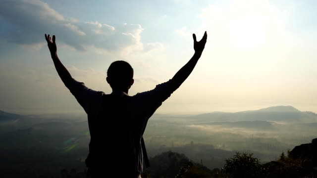 slow motion young man raised arms at the mountaintop view. - actor stock videos & royalty-free footage