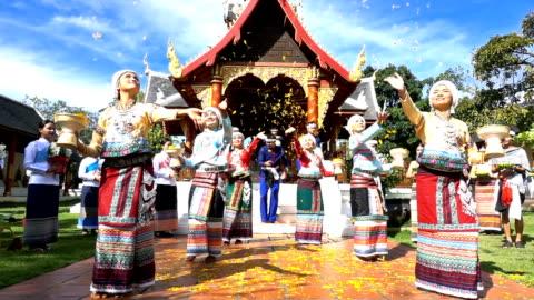 vídeos y material grabado en eventos de stock de lento movimiento de jóvenes, hombres y mujeres desgaste traditionnel tailandés vestido de baile y derraman la flor de la orquídea en el templo - cultura tailandesa