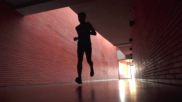 slow motion young men running indoors - endurance stock videos & royalty-free footage