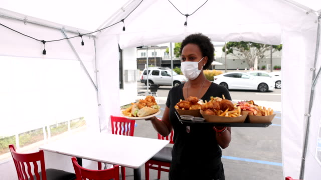 Slow Motion Young Waitress Serving Food to Customers in Outdoor Tent Wearing a Mask