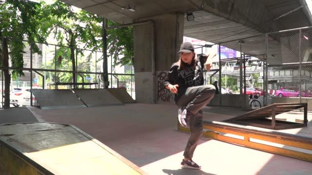 zeitlupe: junge frau beim breakdance unter der brücke - akrobat stock-videos und b-roll-filmmaterial