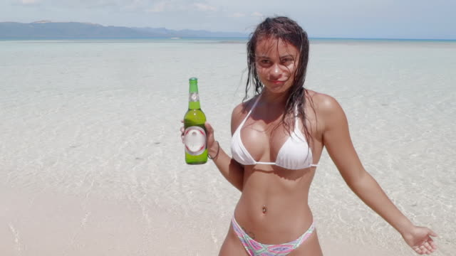 slow motion: young woman in bikini dancing with alcohol bottle in shallow ocean in el limon, dominican republic - belly button piercing stock videos & royalty-free footage