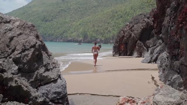 vídeos y material grabado en eventos de stock de slow motion: young woman in bikini on sandy shore among large rocks in el limon, dominican republic - hispaniola