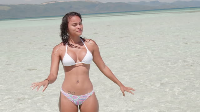 slow motion: young woman in bikini rinsing hands in shallow ocean in el limon, dominican republic - belly button piercing stock videos & royalty-free footage