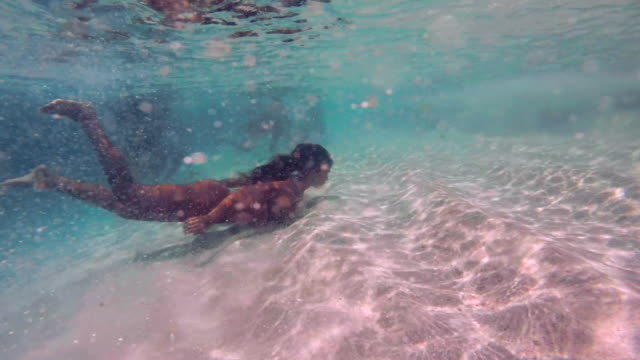 slow motion: young woman in bikini swimming underwater in shallow ocean in el limon, dominican republic - digital camcorder stock videos & royalty-free footage