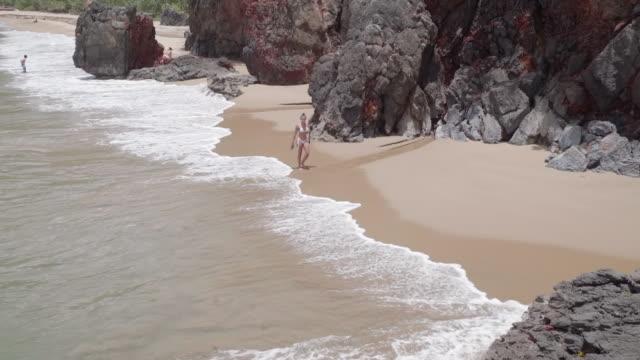 slow motion: young woman in bikini walking on sandy shore with large rocks in el limon, dominican republic - 泡立つ波点の映像素材/bロール