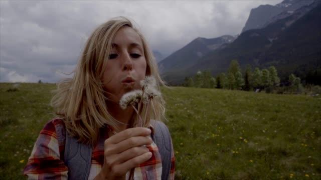vídeos de stock, filmes e b-roll de câmera lenta-jovem mulher está soprando dandelion sementes para o ar - dente de leão