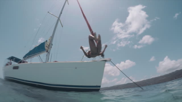 vídeos de stock, filmes e b-roll de slow motion: young woman jumping, front-flip off yacht into ocean in el limon, dominican republic - roupa de natação