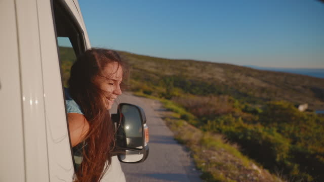 ws slow motion young woman looking out of an open car window. the woman enjoys the ride. - 30 seconds or greater stock videos & royalty-free footage