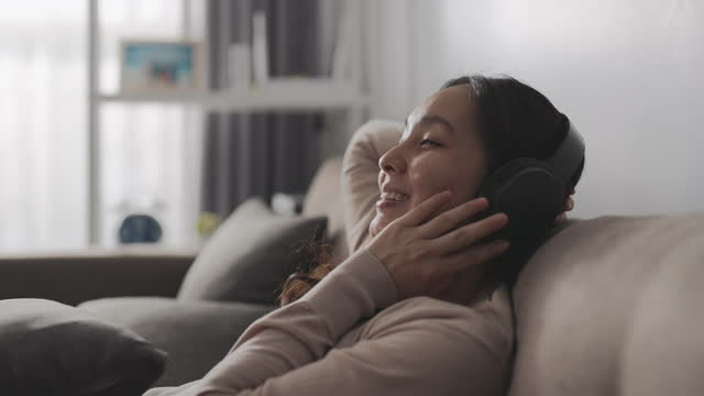 slow motion young woman lying on a sofa, wearing over ear headphones, listening to music - armchair stock videos & royalty-free footage