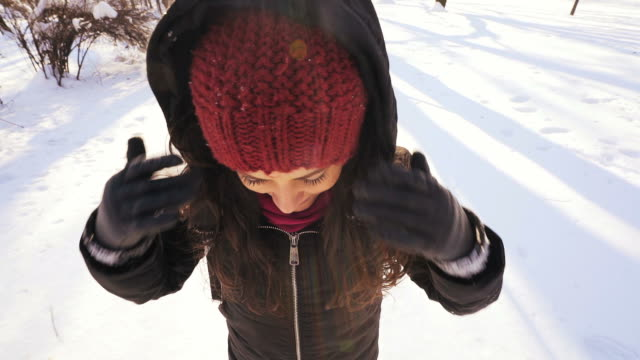 Slow motion: Young woman making snow angels.