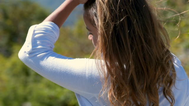 vídeos de stock, filmes e b-roll de slow motion: young woman running hand through long hair blowing in the wind - brown hair