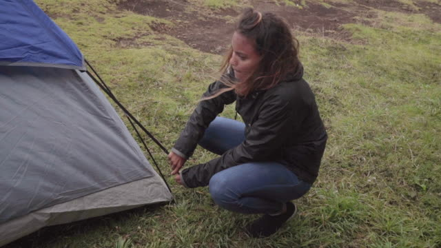 slow motion: young woman setting up tent outdoors on windy day - zelt stock-videos und b-roll-filmmaterial