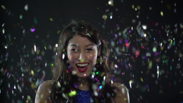 stockvideo's en b-roll-footage met cu slow motion young woman throwing confetti and laughing. - gooien