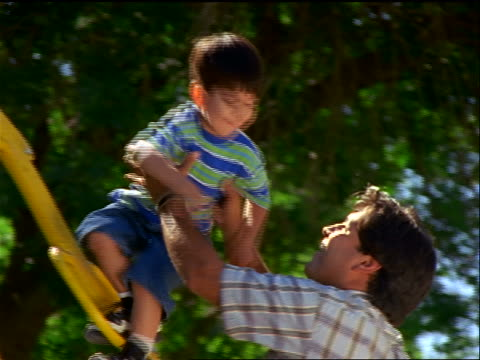 stockvideo's en b-roll-footage met slow motion zoom in hispanic man helping young boy climb down from jungle gym / man kisses + hugs boy - speeltuin