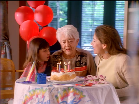 slow motion zoom in hispanic senior woman blowing out candles on birthday cake as woman + granddaughter clap - granddaughter stock videos & royalty-free footage