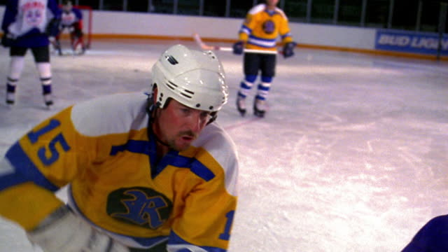 slow motion zoom in male ice hockey player slamming other player against glass wall of rink / players in background