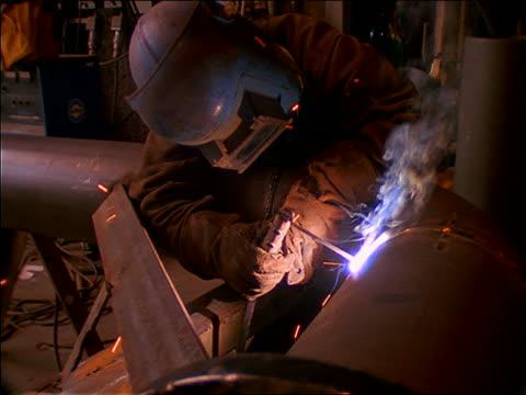 slow motion zoom in person in safety helmet welding metal pipe indoors - welding helmet stock videos & royalty-free footage