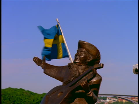 slow motion zoom in to close up of musician statue with swedish flag blowing in background / riddarsholmen, stockholm - swedish flag stock videos and b-roll footage