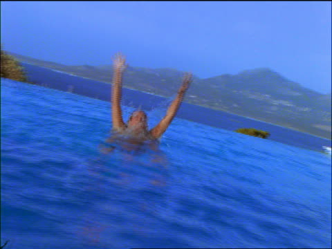 slow motion zoom in to close up woman jumping out of pool - freibad stock-videos und b-roll-filmmaterial