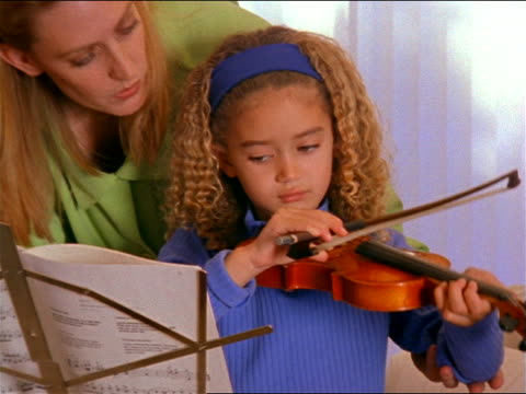 vidéos et rushes de slow motion zoom in woman teaching young girl how to use bow on violin near window - enseignante
