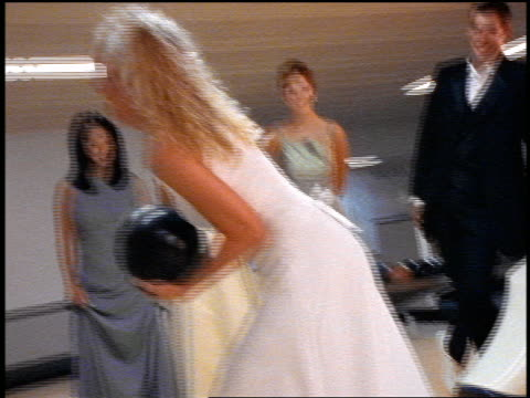 vídeos y material grabado en eventos de stock de slow motion zoom in + zoom out blonde bride preparing to bowl as bridesmaids + ushers watch in bowling alley - bola de bolos