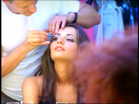 Slow motion zoom in zoom out makeup artist putting eyeshadow on model with cigarette in front of mirror / 2nd model foreground