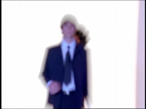 vídeos de stock e filmes b-roll de slow motion zoom in zoom out rack focus male and female models in formalwear walk on catwalk in silhouette + flashing light - desfile de moda