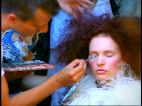 slow motion zoom in zoom out reflection in mirror of hairdresser and makeup artist working on model backstage - hair spray stock videos & royalty-free footage