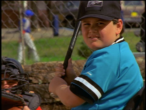 vidéos et rushes de slow motion zoom out from close up boy in wheelchair swinging at ball + missing in baseball game - casquette de baseball
