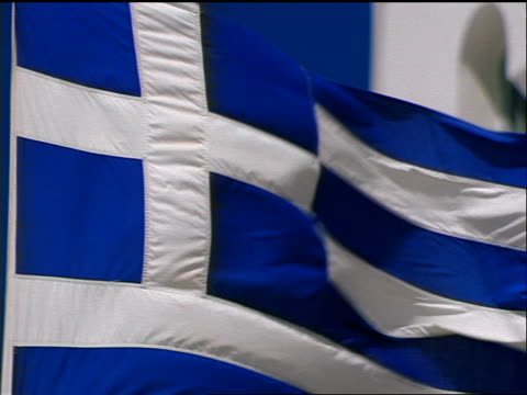 slow motion zoom out from close up greek flag blowing with white stucco building + blue sky in background / santorini, greece - greek flag stock videos & royalty-free footage
