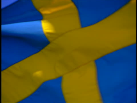 slow motion zoom out from extreme close up of swedish flag blowing in wind / blue sky in background - swedish flag stock videos and b-roll footage