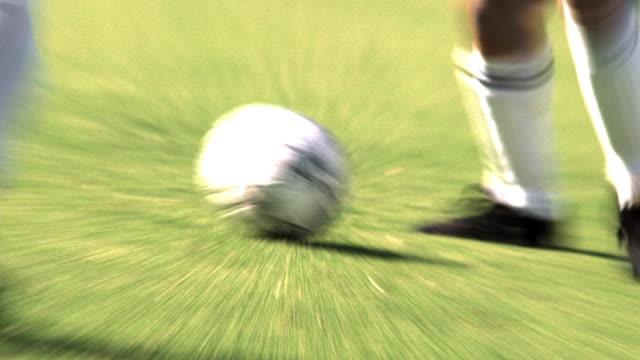 vídeos de stock e filmes b-roll de slow motion ms zi+ zoom out pans legs of soccer players dribbling soccer ball during game on grass field - rasto de movimento