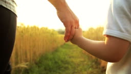 HD Slow motion:Baby boy and his mom taking hands and walking on golden wheat field.