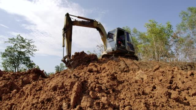 vídeos de stock, filmes e b-roll de câmera lenta, escavadora escava em um chão - cilindro veículo terrestre comercial