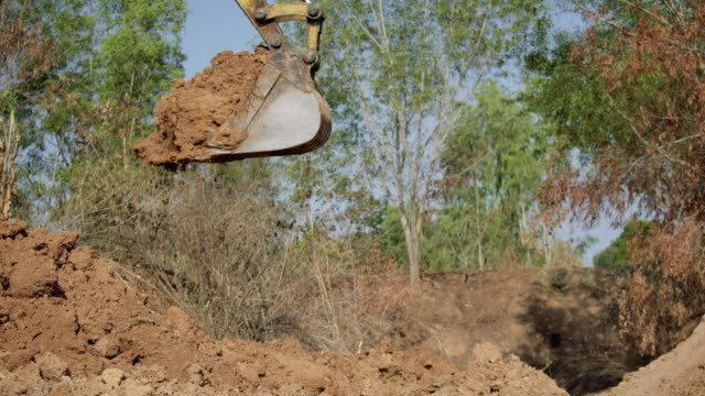 vídeos de stock e filmes b-roll de slow motion,excavator shovel digs into a ground - concha utensílio de servir
