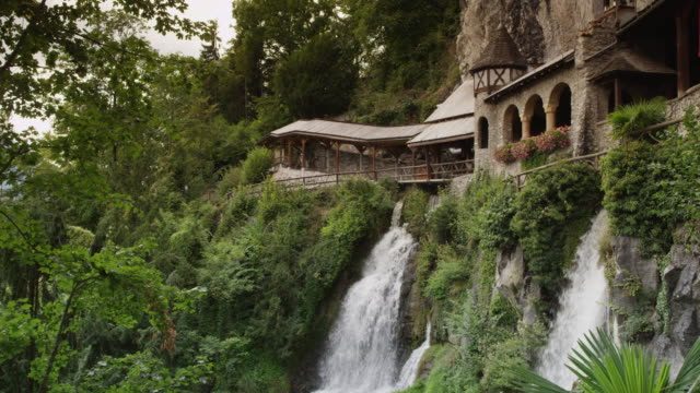 slow motion/medium shot of waterfall and buildings on cliffs / st. beatus caves, switzerland - lake thun stock videos and b-roll footage