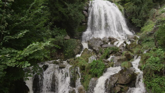 slow motion/medium shot of waterfall and cliff / st. beatus caves, switzerland - lake thun stock videos and b-roll footage