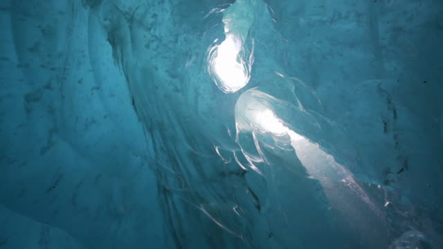 vídeos de stock, filmes e b-roll de slow motion/pan down: water pouring down sunny holes in large glacier onto rocky ground - mendenhall glacier, alaska - profundo