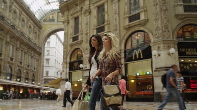 slow motion/panning shot of friends in shopping mall / milan, italy - milano video stock e b–roll