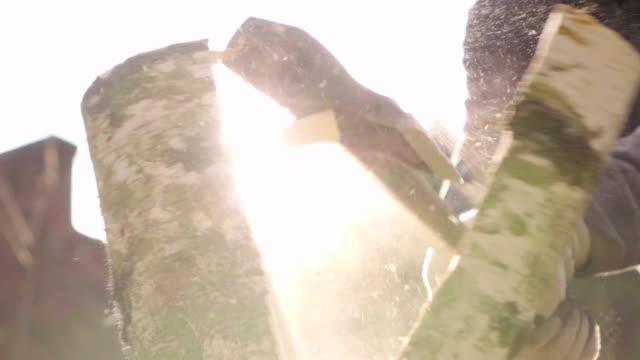 Slow motion: splitsing van hout met een bijl met zon achtergrond