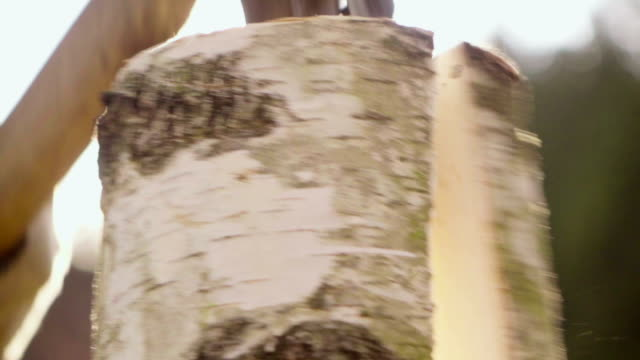 Slow motion:Splitting Wood With An Axe with sun background