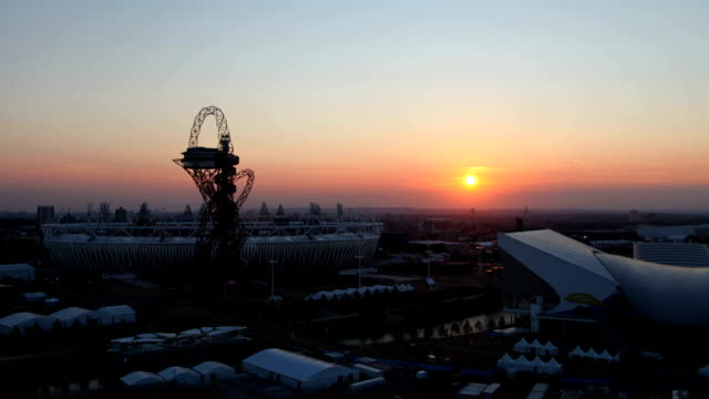 a slow move in while the sunsets over the london 2012 olympic park as the dress rehearsal for the opening ceremony takes place the sun glows red... - 2012 stock videos and b-roll footage