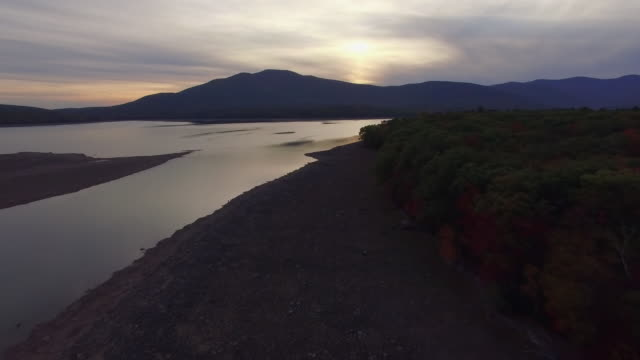 slow moving aerial shot over shoreline of partially drained ashokan reservoir during sunset - reservoir stock videos and b-roll footage