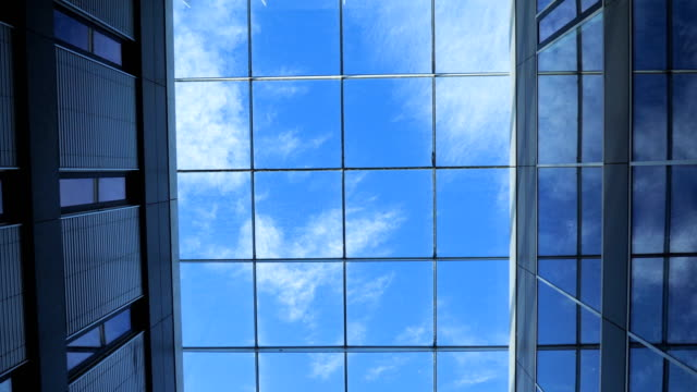 slow moving calming footage of clouds and birds slowing moving across a blue sky. taken looking upward through a sky glass ceiling. - installationskunst stock-videos und b-roll-filmmaterial