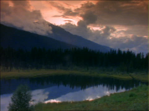 slow moving clouds over mountains with lake in foreground - pinacee video stock e b–roll