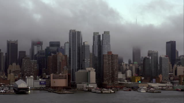 slow moving, dark storm clouds pass above midtown manhattan skyline along hudson river - 42nd street stock videos & royalty-free footage